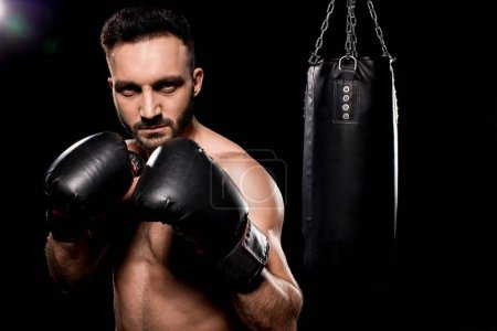Photo for Handsome sportsman wearing boxing gloves standing in boxing poseon black background - Royalty Free Image