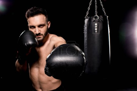 Photo for Shortless sportsman wearing boxing gloves standing in boxing pose on black background - Royalty Free Image