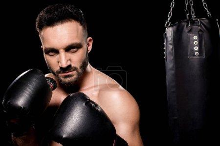 Photo pour Sportif portant des gants de boxe debout dans la posture de boxe isolé sur noir - image libre de droit