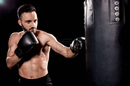 Photo for Bearded sportsman wearing boxing gloves hitting punching bag isolated on black - Royalty Free Image