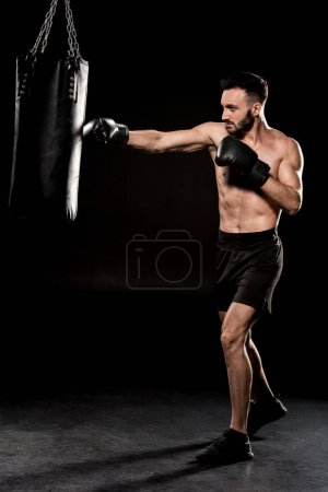 Photo pour Barbu d'athlète avec des gants boxe frappe punching-ball sur fond noir - image libre de droit