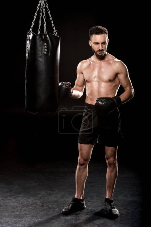 Photo for Thoughtful athlete wearing boxing gloves standing near punching bag on black background - Royalty Free Image