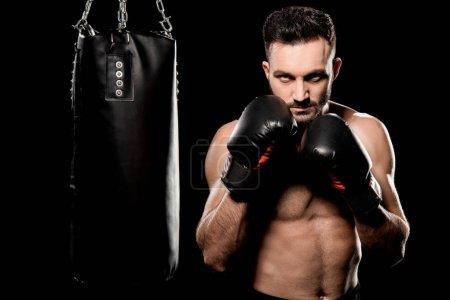 Photo pour Athlète en gants de boxe debout en posture de boxe près d'un sac de boxe isolé sur du noir - image libre de droit
