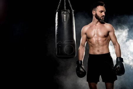 Photo for Pensive athlete in boxing gloves standing near punching bag on black with smoke - Royalty Free Image