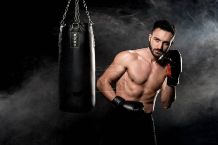 Photo for Handsome sportsman in boxing gloves standing near punching bag on black with smoke - Royalty Free Image