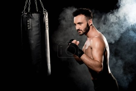 Photo for Muscular athlete standing in boxing pose and looking at punching bag on black with smoke - Royalty Free Image