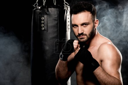 Photo for Muscular fighter standing in boxing pose and looking at camera near punching bag on black with smoke - Royalty Free Image