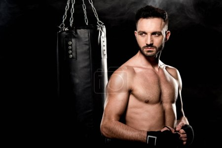 Photo for Athletic boxer standing near punching bag on black with smoke - Royalty Free Image