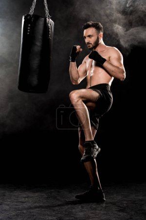Photo for Handsome man exercising near punching bag on black with smoke - Royalty Free Image
