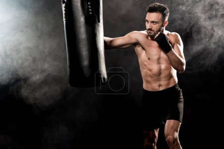 Photo pour Beau boxer athlétique avec sac de boxe sur le noir de fumée - image libre de droit