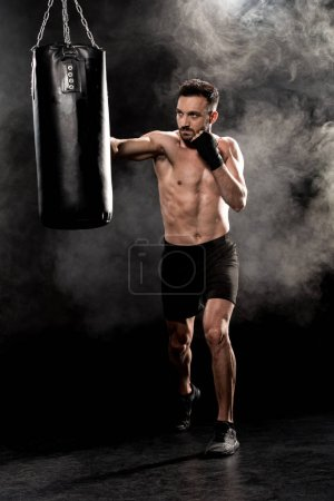 Photo for Shortless athletic boxer kicking punching bag on black with smoke - Royalty Free Image