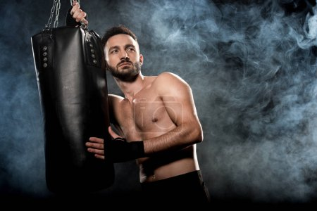 Photo for Pensive athletic boxer holding punching bag on black with smoke - Royalty Free Image