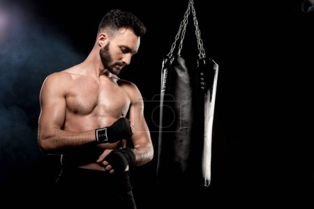 Photo for Handsome athletic boxer wrapping up gloves near punching bag on black background - Royalty Free Image