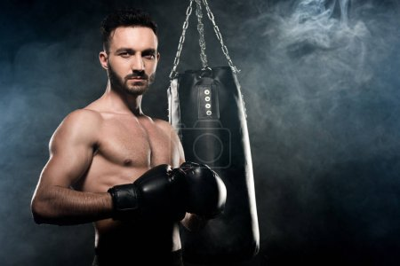 Photo for Handsome athlete standing in boxing pose on black with smoke - Royalty Free Image