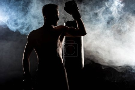 Photo for Silhouette of muscular sportsman in boxing gloves on black with smoke - Royalty Free Image