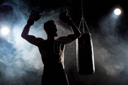 Photo pour Silhouette d'athlète musclé en gants de boxe avec les mains au-dessus de la tête sur noir avec de la fumée - image libre de droit