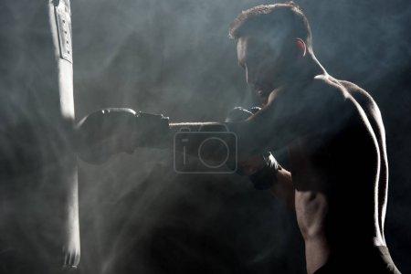 Photo pour Silhouette d'athlète musclé en gants de boxe, sac de boxe sur fond noir avec de la fumée de frapper - image libre de droit