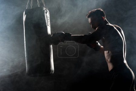 Photo pour Silhouette d'athlète dans les gants de boxe frappe punching-ball sur fond noir avec de la fumée - image libre de droit