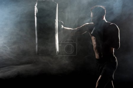 Photo for Silhouette of sportsman in boxing gloves hitting punching bag on black with smoke - Royalty Free Image