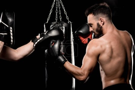 Photo for Handsome boxer fighting with man in punching gloves isolated on black - Royalty Free Image