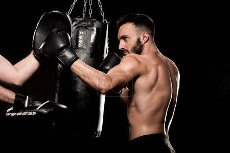Photo pour Beau sportif de combat avec l'homme dans le poinçonnage gants isolés sur fond noir - image libre de droit