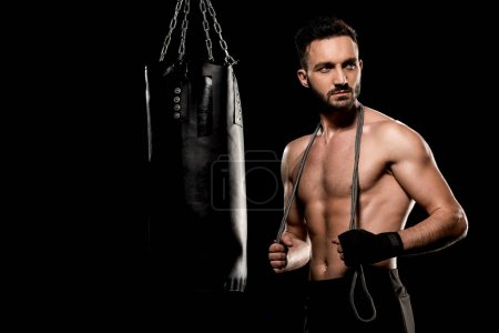 Photo for Handsome boxer standing with jumping rope near punching bag isolated on black - Royalty Free Image