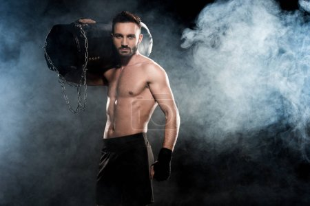 Photo for Muscular boxer holding punching bag on shoulder on black with smoke - Royalty Free Image