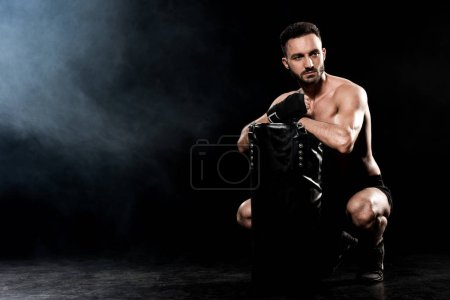 Photo for Shortless man sitting and holding punching bag on black with smoke - Royalty Free Image