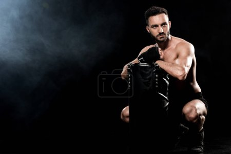 Photo for Shortless boxer sitting and holding punching bag on black with smoke - Royalty Free Image