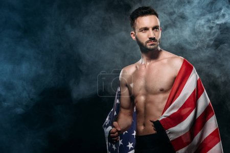 Photo for Handsome shortless athlete holding american flag on black with smoke - Royalty Free Image