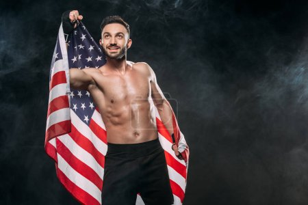 Photo for Happy athlete holding american flag on black with smoke - Royalty Free Image