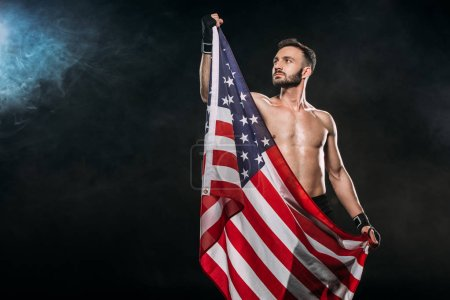 Photo for Handsome sportsman holding american flag on black with smoke - Royalty Free Image