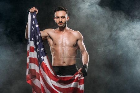 Photo for Shortless athlete holding american flag on black with smoke - Royalty Free Image