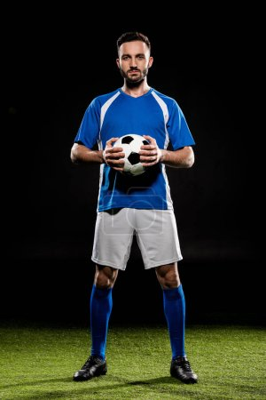 Photo for Football player standing with ball on green grass isolated on black - Royalty Free Image