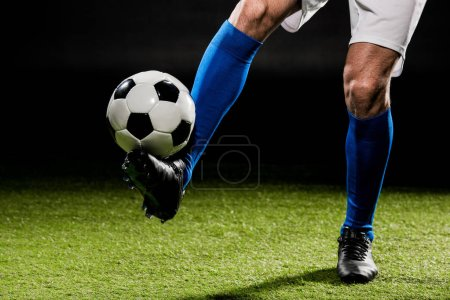 Photo for Cropped view of sportsman playing with ball on grass isolated on black - Royalty Free Image