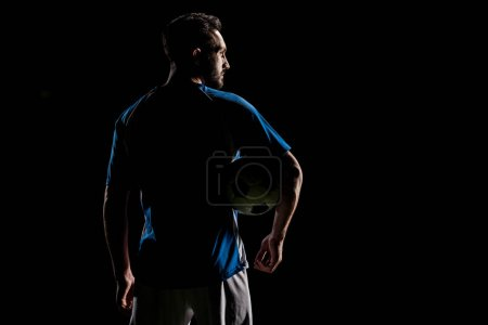 Photo for Silhouette of muscular sportsman holding ball isolated on black - Royalty Free Image
