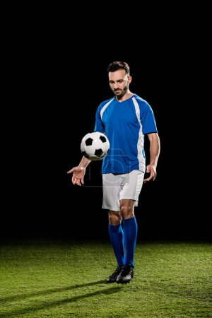Photo for Bearded sportsman in uniform training with ball on grass isolated on black - Royalty Free Image