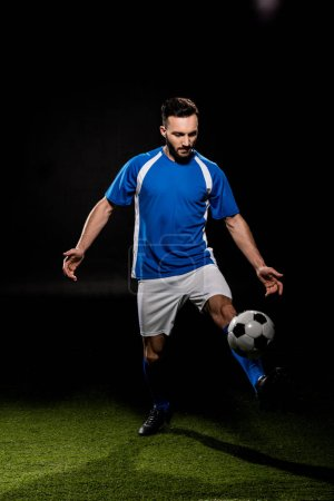 Photo for Bearded football player in uniform training with ball on grass isolated on black - Royalty Free Image