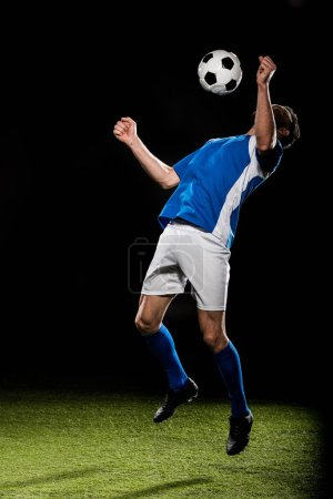 Photo for Bearded football player in uniform jumping with ball isolated on black - Royalty Free Image