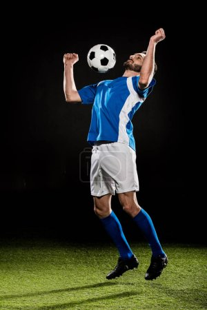 Photo for Handsome football player in uniform jumping with ball isolated on black - Royalty Free Image