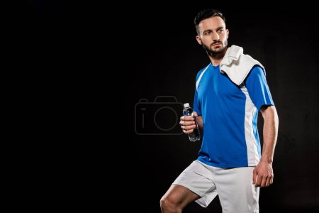 Photo for Handsome man in uniform standing with towel on shoulder and holding bottle with water isolated on black - Royalty Free Image