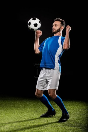 Photo pour Footballeur sportif en uniforme sautant avec balle isolée sur noir - image libre de droit