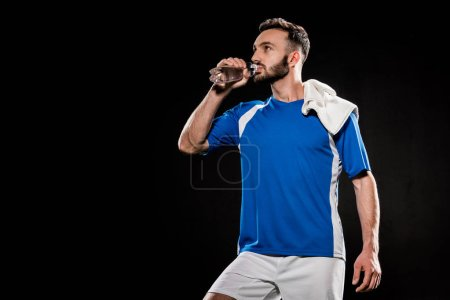 Photo for Bearded man in uniform standing with towel on shoulder and drinking water from bottle isolated on black - Royalty Free Image
