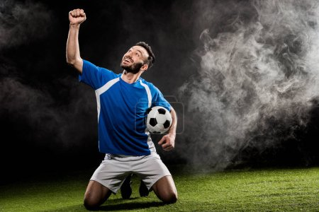 Photo for Cheerful football player celebrating victory and holding ball on black with smoke - Royalty Free Image
