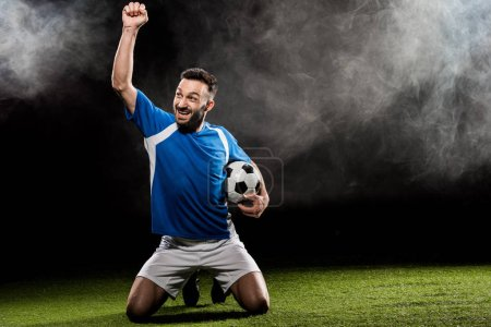 Photo for Happy football player celebrating victory and holding ball on black with smoke - Royalty Free Image