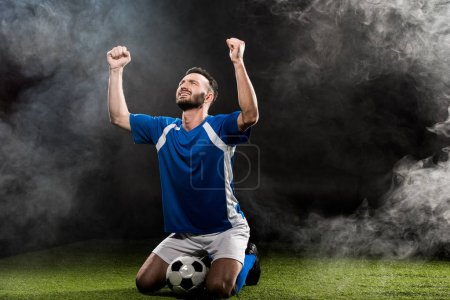handsome football player celebrating victory while sitting on grass on black with smoke