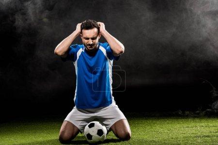 Photo pour Beau joueur de football tenant la tête tout en étant assis sur l'herbe sur noir avec de la fumée - image libre de droit