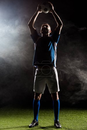 Photo for Silhouette of football player holding ball above head on black with smoke - Royalty Free Image