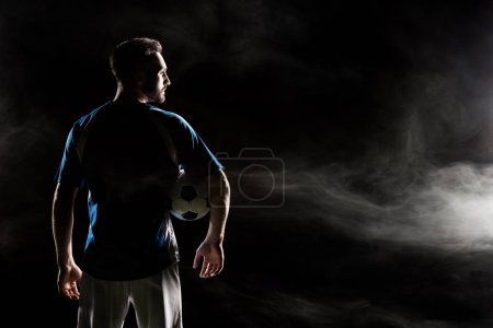 Photo for Silhouette of football player holding ball on black with smoke - Royalty Free Image