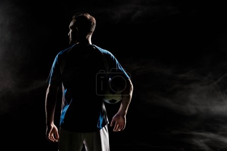 Photo for Silhouette of football player standing with ball on black with smoke - Royalty Free Image